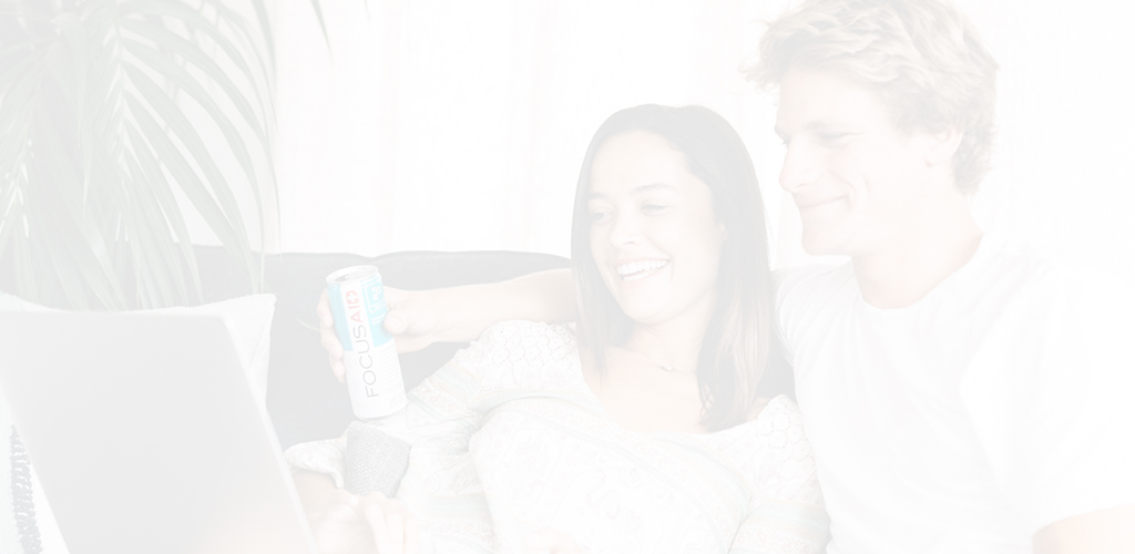 lifestyle header image of couple relaxing at home on their couch with a can of FOCUSAID, while perusing the internet together on their laptop